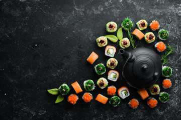 Sushi background. Assortment of Japanese food, sushi and tea on a black stone background. Top view. Free space for your text.