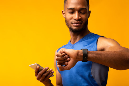 Headshot of afro guy looking at his wrist watch