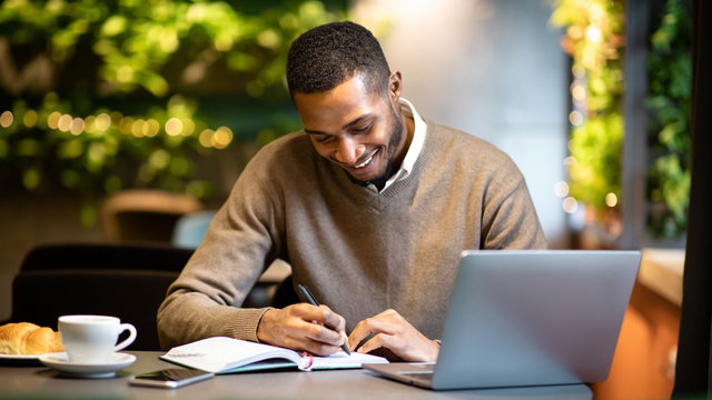 Black man writing in notebook sitting at cafe