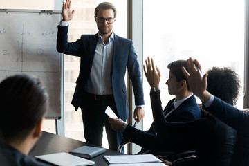 Confident businessman mentor raising hand with colleague question in boardroom.