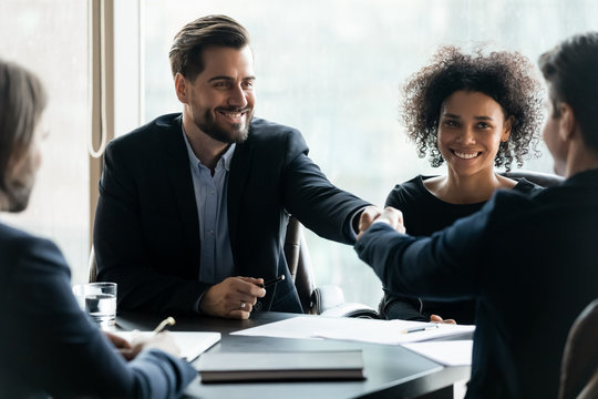Happy successful businessman in suit shaking hand of business partner.