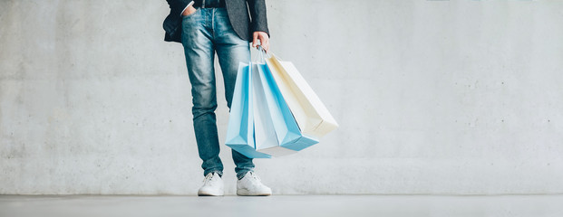 Men fashion clothing store. Advertisement promotion. Guy in smart casual outfit holding paper bags.