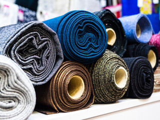 Stores à enrouleur Tissu Rolls of shiny knitted fabric for sewing evening and ball gowns close-up. A selection of different beautiful fabrics for sewing fashion collections of clothing. Factory fabrics in stock