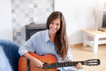 Young woman plays guitar. Happy girl enjoying music. Female musician smiling in living room at home.