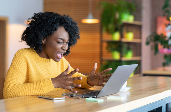 Angry black businesswoman screaming at laptop screen