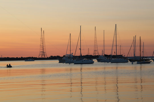 Sunrise over the water with sailboats