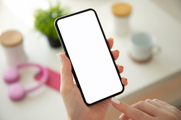female hands holding phone with isolated screen in room