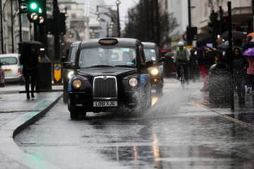 London Black taxicab's drive through a puddle on Oxford Street during Storm Dennis in London