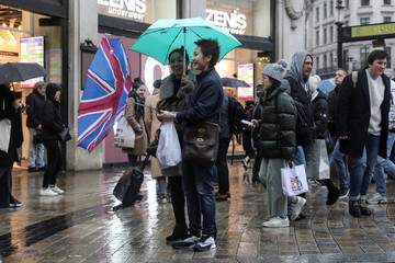 A pedestrian's Union flag umbrella is turned inside out by the wind at Oxford Street during Storm Dennis in London