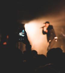 Public prenant en photo au téléphone un artiste sur scène lors d'un concert de rap français