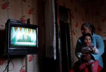 Roma people watch Prime Minister Viktor Orban's state of the nation speech in Saly