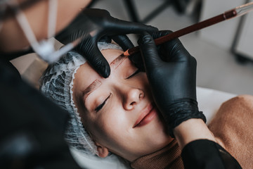 Eyebrows microblading concept. Cosmetologist preparing young woman for eyebrow permanent makeup procedure.