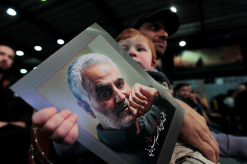 A supporter of Lebanon's Hezbollah leader Sayyed Hassan Nasrallah carries a child holding a picture of the late Iran's Quds Force top commander Qassem Soleimani during a rally commemorating in Beirut's southern suburbs