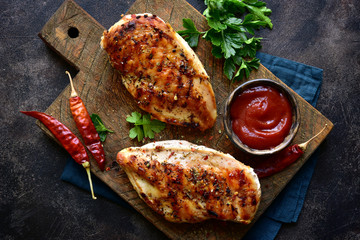Grilled chicken fillet with spicy ketchup. Top view with copy space.