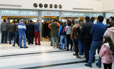 People queue to buy flight tickets at the Lebanese Middle East Airlines (MEA) offices in Beirut international airport