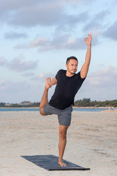 Young yoga man wearing black t-shirt at the beach, relaxing, breathing and meditating in a natural environment with palm trees and ocean as background.