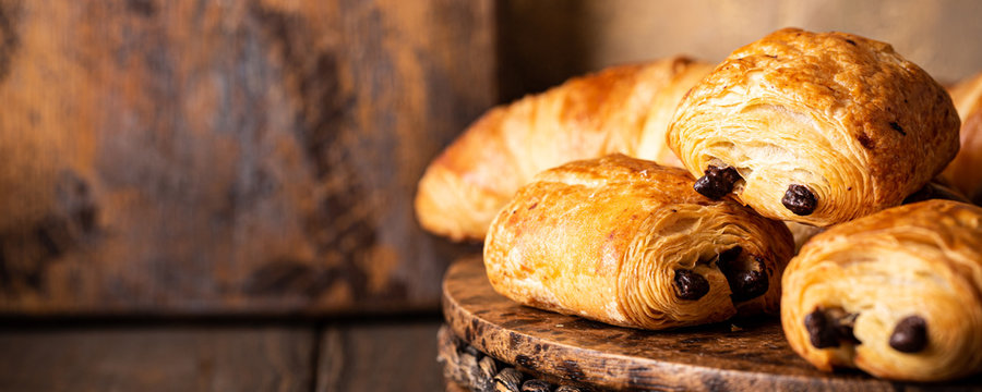 Freshly baked sweet buns puff pastry with chocolate and croissants on old wooden background. Breakfast or brunch concept with copy space, banner.