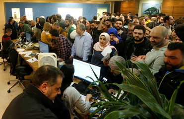 People wait to buy flight tickets at the Lebanese Middle East Airlines (MEA) offices in Beirut international airport