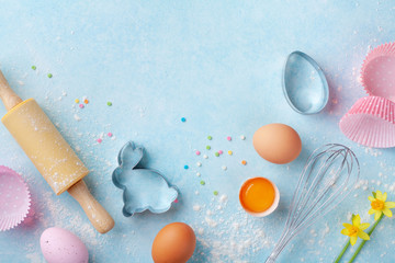 Easter baking background with rolling pin, whisk, eggs, flour and colorful confetti on blue table top view. Flat lay.