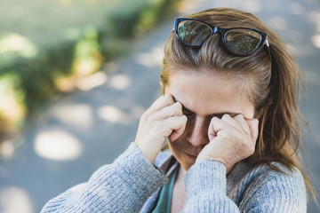 Woman with headache rubbing her eyes outside Fotomurales