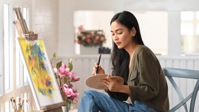 Woman Artist Works on Abstract acrylic painting in the art studio.