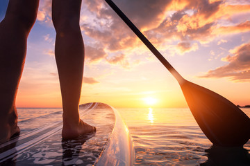 Stand up paddle boarding or standup paddleboarding on quiet sea at sunset with beautiful colors...