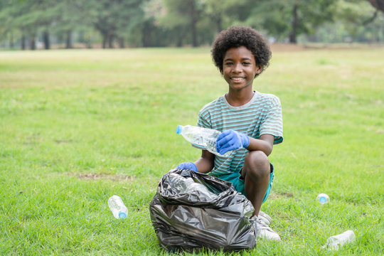 African American boy volunteer smiling picking up plastic bottles into a black garbage bag, help garbage collection charity environment