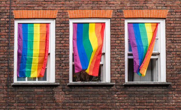Flying lgbtq flags hanging from three windows
