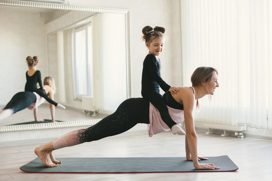 Sporty woman and child girl doing stretching exercise on yoga mat in front of mirror in fitness class