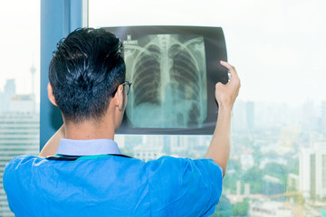 Young Asian doctor holding an X-Ray film near a window.