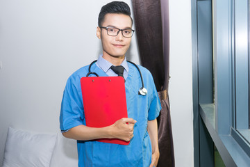 Young Asian doctor with medical clipboard bed head ticket and stethoscope on his shoulder.