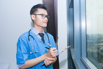Young Asian doctor writing his medical report and look out in front of window.