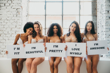 Group of women with different body and ethnicity posing together to show the woman power and...