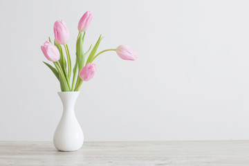 Foto op Plexiglas Bloemen pink tulips in white ceramic vase on wooden table on background white wall