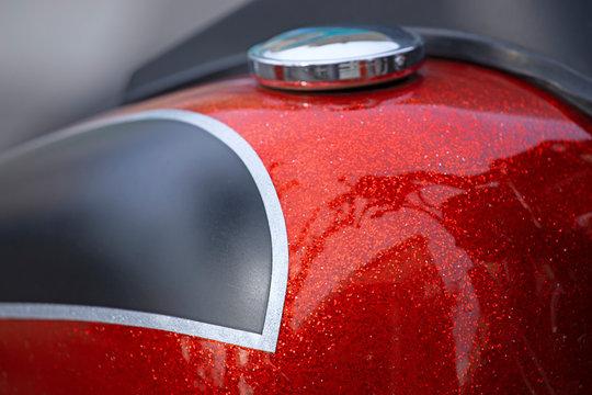 Réservoir customisé rouge métallisé de moto grosse cylindrée.