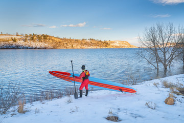 active senior is carrying stand up paddleboard in winter
