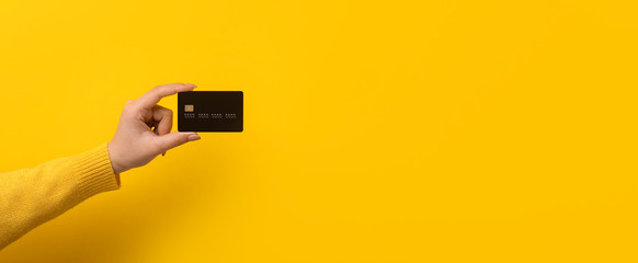 bank card in hand over yellow background, panoramic mock-up