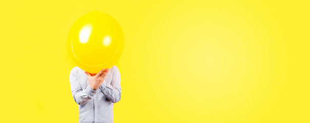 man holding yellow balloon. Positive thinking concept, image on a yellow background, panoramic mock-up with space for text