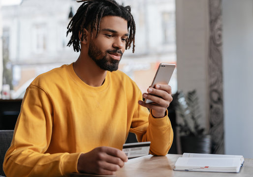 African American man holding credit card, using smartphone for online shopping, mobile banking. Young freelancer receive payment, check balance. Pensive hipster ordering food online, booking tickets