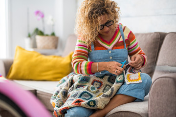 Busy woman at home working like a tailor with coloured old style fashion fabric - handmade production of artistic clothes - active alternative middle age people concept