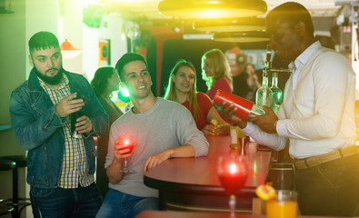 Group of male friends with alcohol in nightclub