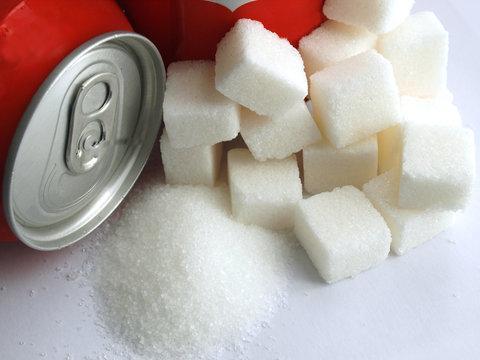 sugar adiction: close up of red soda softdrink cans and sugar