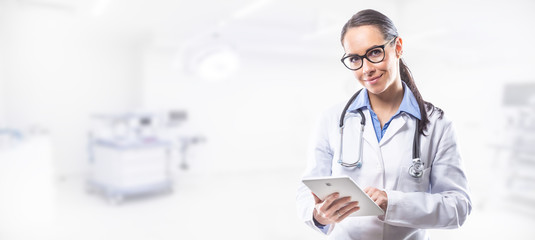 Medical doctor woman holding tablet pc in front of surgery room