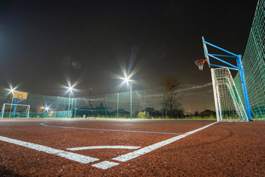 Outdoors mini football and basketball court with ball gate and basket surrounded with high protective fence brightly illuminated with spotlight lamps at night.