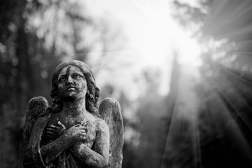 Fotomurales - Black and white dramatic image of ancient statue of angel of death as symbol of end of life.