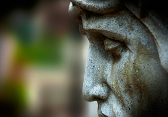 Fotomurales - Close up fragment of ancient statue of crucifixion of Jesus Christ in profile against blur background