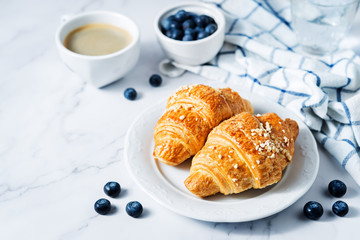 Fresh croissants with berries and cup of coffee