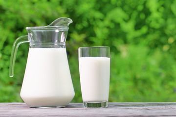 Jug and glass of milk on a wooden table