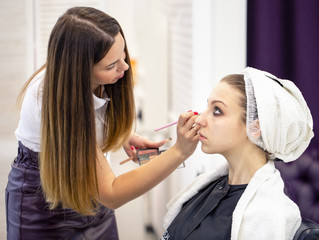 Makeup artist in a white blouse applies makeup to young girl