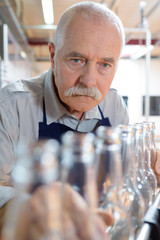 senior looking at water bottles on production line